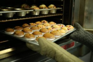 Cupcakes being taken from oven